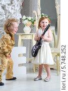 Мальчик и девочка в костюмах в стиле ретро с гитарой в интерьере. Стоковое фото, фотограф Losevsky Pavel / Фотобанк Лори