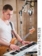 Купить «Музыкант с бас-гитарой играет на синтезаторе в студии звукозаписи», фото № 5748528, снято 25 декабря 2012 г. (c) Losevsky Pavel / Фотобанк Лори