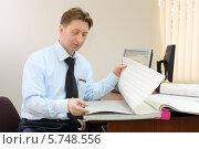 Купить «Мужчина сидит в офисе и листает альбом с образцами обоев», фото № 5748556, снято 2 декабря 2012 г. (c) Losevsky Pavel / Фотобанк Лори