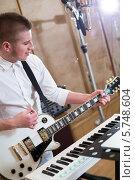 Купить «Гитарист, играет на гитаре рядом с синтезатором в студии», фото № 5748604, снято 25 декабря 2012 г. (c) Losevsky Pavel / Фотобанк Лори