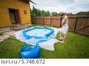 Купить «Женщина накачивает надувной бассейн во дворе загородного дома», фото № 5748672, снято 16 июня 2013 г. (c) Losevsky Pavel / Фотобанк Лори