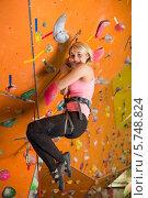 Купить «Женщина с альпинистским снаряжением висит на фоне скалдрома», фото № 5748824, снято 5 декабря 2012 г. (c) Losevsky Pavel / Фотобанк Лори
