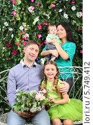 Купить «Счастливая молодая семья с двумя детьми сидит на плетеной скамейке», фото № 5749412, снято 13 января 2013 г. (c) Losevsky Pavel / Фотобанк Лори
