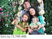 Купить «Счастливая молодая семья на цветочных качелях в саду», фото № 5749440, снято 13 января 2013 г. (c) Losevsky Pavel / Фотобанк Лори
