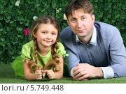 Купить «Молодой отец с дочкой около живой изгороди», фото № 5749448, снято 13 января 2013 г. (c) Losevsky Pavel / Фотобанк Лори