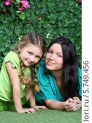 Купить «Красивая молодая девушка со своей дочкой на фоне живой изгороди», фото № 5749456, снято 13 января 2013 г. (c) Losevsky Pavel / Фотобанк Лори