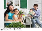 Купить «Счастливая молодая семья отдыхает около своего коттеджа», фото № 5749524, снято 13 января 2013 г. (c) Losevsky Pavel / Фотобанк Лори