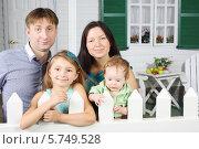 Купить «Счастливая семья около забора на фоне нового коттеджа», фото № 5749528, снято 13 января 2013 г. (c) Losevsky Pavel / Фотобанк Лори