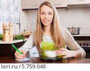 Купить «Счастливая домохозяйка взвешивает муку на кухне дома», фото № 5759048, снято 28 февраля 2014 г. (c) Яков Филимонов / Фотобанк Лори