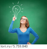 Купить «Привлекательная молодая женщина в повседневной одежде и в очках показывает пальцем на нарисованную на зеленой доске лампу», фото № 5759840, снято 5 декабря 2013 г. (c) Syda Productions / Фотобанк Лори