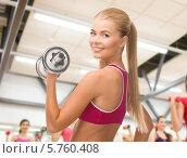 Купить «Привлекательная девушка выполняет упражнение на разгибание в локтевом суставе руки с гантелью в спортивном зале», фото № 5760408, снято 23 марта 2013 г. (c) Syda Productions / Фотобанк Лори