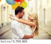Купить «Молодой мужчина и девушка с разноцветными воздушными шариками обнимаются на улице города», фото № 5760460, снято 14 июля 2013 г. (c) Syda Productions / Фотобанк Лори