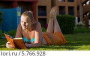 Купить «Женщина читает книгу, лёжа на траве», видеоролик № 5766928, снято 25 февраля 2014 г. (c) Данил Руденко / Фотобанк Лори