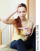 Купить «Девушка смотрит на тест на беременность», фото № 5767168, снято 20 июня 2013 г. (c) Яков Филимонов / Фотобанк Лори