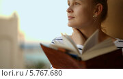 Купить «Задумчивая девушка с книгой», видеоролик № 5767680, снято 24 марта 2014 г. (c) Данил Руденко / Фотобанк Лори