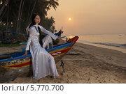 Купить «Девушка в национальной вьетнамской одежде и в лодке», фото № 5770700, снято 19 января 2014 г. (c) макаров виктор / Фотобанк Лори