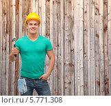 Молодой рабочий в каске держит в руке молоток, стоя на фоне деревянной стены. Стоковое фото, фотограф Syda Productions / Фотобанк Лори