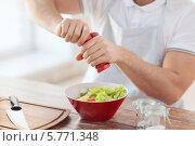 Мужчина солит овощной салат в миске. Стоковое фото, фотограф Syda Productions / Фотобанк Лори