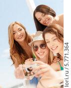 Купить «Веселые подруги фотографируются на пляже в солнечный день», фото № 5771364, снято 4 июля 2013 г. (c) Syda Productions / Фотобанк Лори