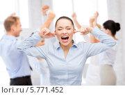 Купить «Стресс. Женщина кричит, заткнув уши пальцами на фоне коллег в орфисе», фото № 5771452, снято 8 декабря 2013 г. (c) Syda Productions / Фотобанк Лори