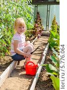 Маленькая девочка ухаживает за растениями в теплице. Стоковое фото, фотограф Марина Славина / Фотобанк Лори
