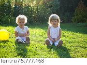 Две милые маленькие девочки сидят на траве, контровый свет. Стоковое фото, фотограф Евдокимова Ольга / Фотобанк Лори
