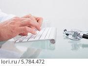 Купить «врач что-то печатает на компьютерной клавиатуре», фото № 5784472, снято 25 января 2014 г. (c) Андрей Попов / Фотобанк Лори