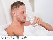 Купить «мужчина лежит в постели и пьет воду», фото № 5784556, снято 25 января 2014 г. (c) Андрей Попов / Фотобанк Лори