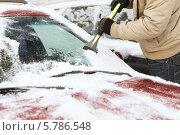 Купить «Мужчина очищает скребком от снега лобовое стекло автомобиля», фото № 5786548, снято 16 января 2014 г. (c) Syda Productions / Фотобанк Лори