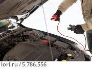 Купить «Открытый капот автомобиля. Попытка запустить двигатель с помощью проводов вспомогательного запуска», фото № 5786556, снято 16 января 2014 г. (c) Syda Productions / Фотобанк Лори