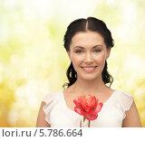 Милая брюнетка с красным цветком в руках. Стоковое фото, фотограф Syda Productions / Фотобанк Лори