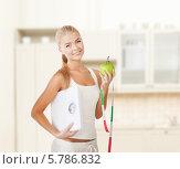 Купить «Концепция здорового образа жизни. Девушка с весами и зеленым яблоком в руках», фото № 5786832, снято 23 марта 2013 г. (c) Syda Productions / Фотобанк Лори