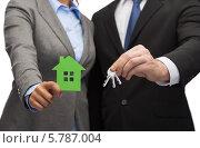 Купить «Мужчина и женщина в деловых костюмах держат в руках вырезанный из бумаги зеленый домик и ключи», фото № 5787004, снято 12 декабря 2013 г. (c) Syda Productions / Фотобанк Лори