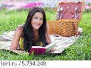 Красивая девушка лежит на траве с книгой и улыбается. Стоковое фото, фотограф Виктория Чеканова / Фотобанк Лори