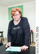 Купить «Пенсионерка с квитанциями стоит около стола и смотрит в камеру», фото № 5795900, снято 23 марта 2014 г. (c) Кекяляйнен Андрей / Фотобанк Лори
