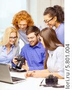 Купить «Молодые коллеги в офисе работают с фотоаппаратом и ноутбуком», фото № 5801004, снято 1 февраля 2014 г. (c) Syda Productions / Фотобанк Лори