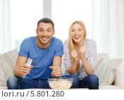 Купить «Молодые мужчина и женщина на диване с миской покорна увлеченно смотрят телевизор», фото № 5801280, снято 9 февраля 2014 г. (c) Syda Productions / Фотобанк Лори