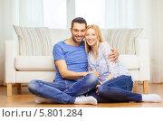 Счастливая влюбленная пара. Молодой человек и девушка сидят на полу дома. Стоковое фото, фотограф Syda Productions / Фотобанк Лори