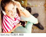Купить «Позитивная девушка в наушниках слушает музыку и улыбается, сидя на земле, прислонившись к стене. Вид сверху», фото № 5801400, снято 20 июля 2013 г. (c) Syda Productions / Фотобанк Лори
