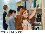 Купить «Улыбающаяся студентка выбирает книгу на библиотечной полке», фото № 5812984, снято 23 марта 2014 г. (c) CandyBox Images / Фотобанк Лори