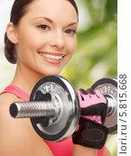 Купить «Спортивная красивая девушка улыбается, выполняя упражнения с тяжелой гантелью», фото № 5815668, снято 12 января 2013 г. (c) Syda Productions / Фотобанк Лори
