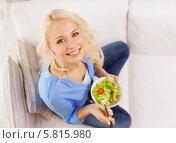 Красивая девушка сидит на диване и ест овощной салат. Стоковое фото, фотограф Syda Productions / Фотобанк Лори