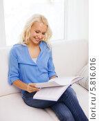 Купить «Привлекательная молодая женщина отдыхает дома на диване с книгой в руках», фото № 5816016, снято 6 февраля 2014 г. (c) Syda Productions / Фотобанк Лори