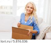 Блондинка улыбаясь распаковывает посылку дома, сидя на диване. Стоковое фото, фотограф Syda Productions / Фотобанк Лори