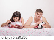 Купить «Девушка красит ногти в кровати, парень смотрит футбол», фото № 5820820, снято 23 марта 2014 г. (c) Иванов Алексей / Фотобанк Лори