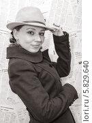 Купить «Молодая женщина в шляпе и пальто напротив фона из газет, черно-белая фотография», фото № 5829640, снято 10 апреля 2014 г. (c) Кекяляйнен Андрей / Фотобанк Лори