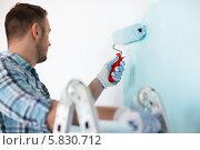 Мужчина делает ремонт в квартире - красит стены, стоя на стремянке. Стоковое фото, фотограф Syda Productions / Фотобанк Лори