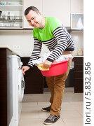 Купить «Симпатичный мужчина кладет белье в стиральную машину», фото № 5832856, снято 5 июня 2020 г. (c) Дарья Филимонова / Фотобанк Лори