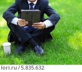 Купить «Мужчина в офисном костюме сидит на траве с электронным планшетом в руке», фото № 5835632, снято 6 августа 2013 г. (c) Дарья Петренко / Фотобанк Лори