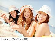 Купить «Привлекательные девушки в летних шляпах загорают на пляже», фото № 5842688, снято 11 июля 2013 г. (c) Syda Productions / Фотобанк Лори